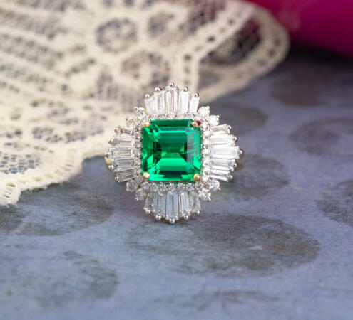 Custom yellow gold engagement ring with emerald center and halo of diamond accents